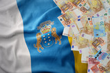 euro money banknotes on the waving national flag of canary islands.