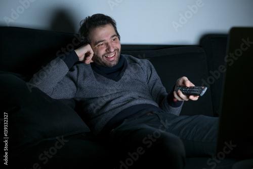 Juliste Smiling man watching television at night