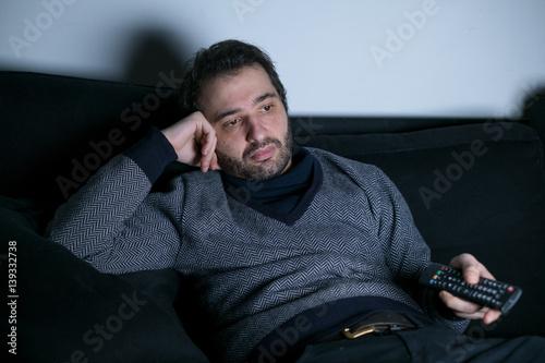 Plagát Man watching television at night