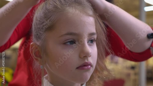 Little blond kid in barbershop. Woman hairdresser make hairstyle baby with long hair