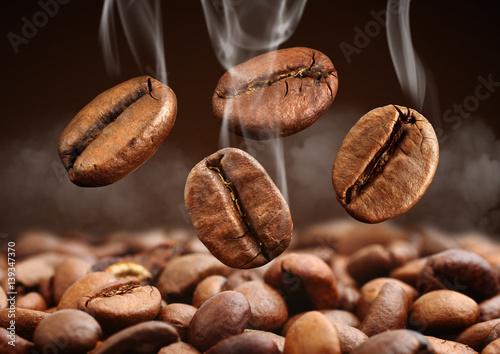 Closeup falling coffee bean with smoke on brown background