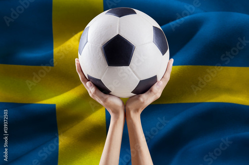 Arms holding ball with flag of Sweden Poster