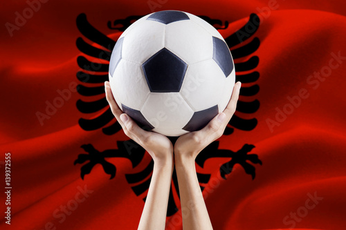Poster Arms lifting ball with flag of Albania