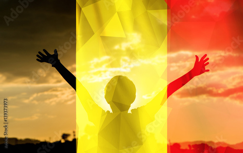 Young man raising his hands on a sunset background with a flag background - 139373973