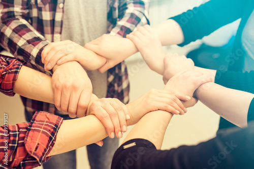 A group of young people hold strong hands.