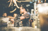 Fototapety Blurred defocused side view of barman and people drinking and having fun at cocktail bar - Social gathering concept with people enjoying time together - Warm retro contrast filter with focus on shaker