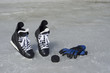 Black hockey skates, gloves and puck on the spring ice in sunny day