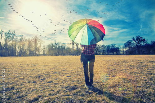 woman holding rainbow umbrella and watching sunset in the nature, birds flying a Poster