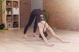 Young Caucasian woman practicing yoga doing downward facing dog position