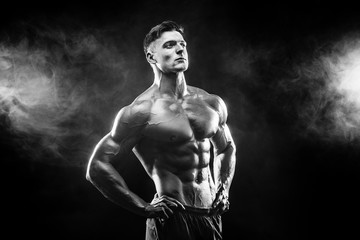 Strong bodybuilder man with perfect body- abs, shoulders, biceps, triceps, chest posing in studio smoke background © zamuruev