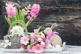 Osterkarte mit Osterhase-Schneeglöckchen-Ostereier-Hyazinthe und Frühlingsstrauß rustikal vor Holzhintergrund