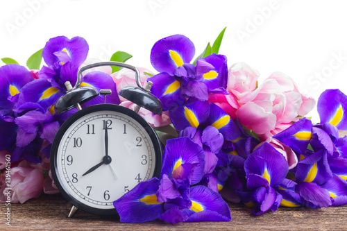 Spring time concept - retro alarm clock with fresh flowers