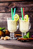 Two clear glasses of organic fresh homemade kiwi and banana smoothie on a wooden background. Healthy lifestyle drink for breakfast, lunch. Vegetarian and diet food.