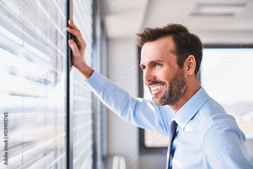 Foto Murales Happy businessman in office looking out the window
