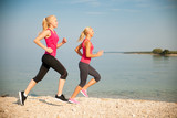 two women athlets  running on the beach - early morning summer workout