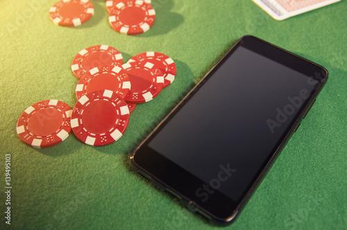 Smartphone on green gambling cloth next to poker chips плакат