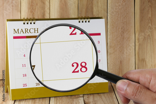 Poster Magnifying glass in hand on calendar you can look Twenty-eight day of month,Focus number Twenty-eight in March