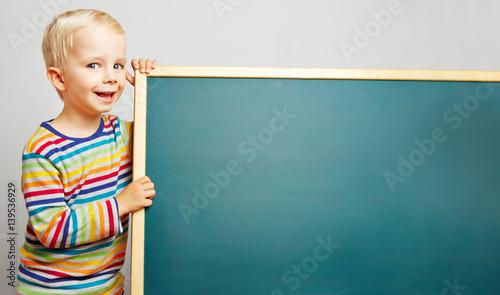 Lachender Junge neben leerer Tafel