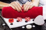 beautiful red manicure with red orchid flower and towel on the black wooden table.