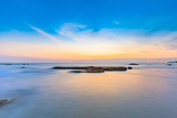 Long exposure shot of calmness sea and the rock in beautiful sunset sky