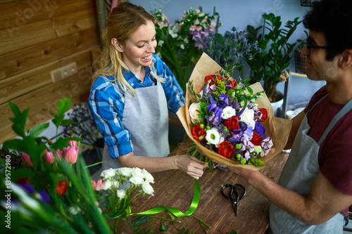 Young man and woman working in flower shop