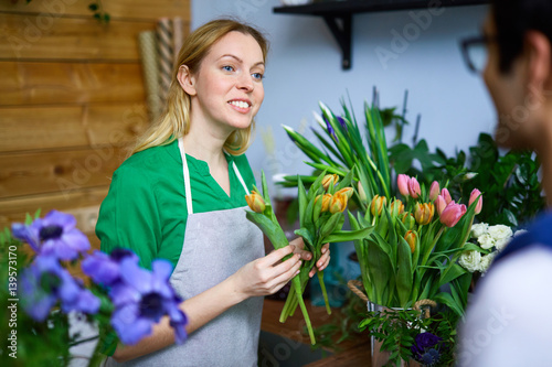 Young woman helping guy to choose tulips for his girlfriend in flower-shop