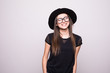 Fashionable brunette wearing bright black clothes holding her hat with eyesglasses isolated on grey
