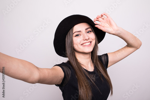 Poster Charming beautiful woman take selfie from hands on grey
