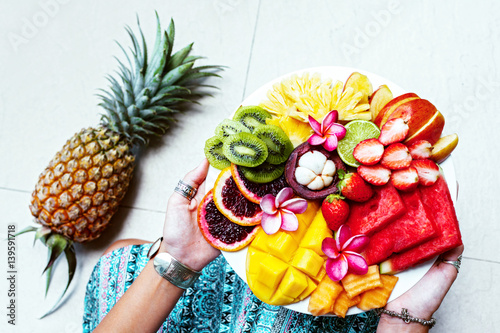 Hands holding fresh fruit plate