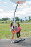 Ladies leaning against post of basketball net