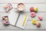 Business working place: hot chocolate with marshmallow, macarons, candies and notebook with pen on white wooden boards