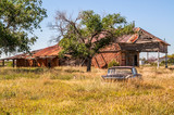 Overgrown field with an abandoned car and an old gas station and motel