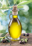 Olive oil and berries are on the wooden table under the olive tree. - 139662162