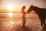 Prett lady stroking her beloved horse