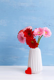 Gerbera flowers in vase on blue wood vintage background. 8 march or Valentines day love design with red heart. Painted wooden planks.