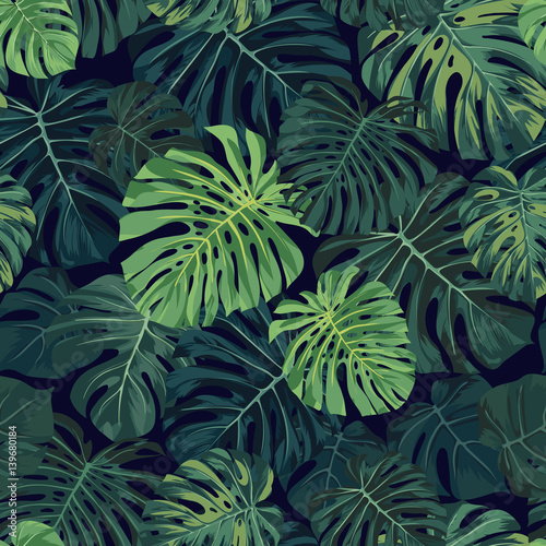 Seamless vector tropical pattern with green monstera palm leaves on dark background. Exotic hawaiian fabric design. © Ms.Moloko