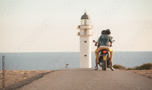 couple ride a bike by the lighthouse