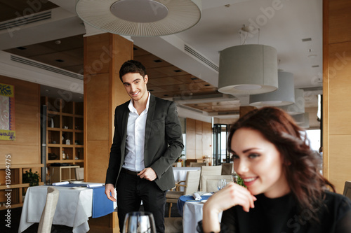 Happy Woman in restaurant with man on background