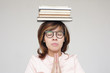 Girl meditates with a pile of books on head. Preparing for the exam, or reading books