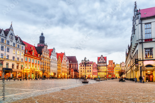 Zdjęcia na płótnie, fototapety na wymiar, obrazy na ścianę : Wroclaw, polish historical city center, Poland. Market square place, old medieval buildings architecture, at dramatic sky background, evening twilight scene. Popular travel destination.