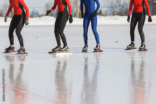 Speed skating competition on ice rink at winter sunny day - sportsmen ready for Poster