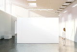 Woman walking near blank white wall mockup in modern gallery. Girl admires a clear big stand mock up in museum with contemporary art exhibitions. Large hall interior, banner exposition show - 139706194
