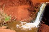 Ein Wasserfall gräbt sich durch rotes Gestein im Waimea Canyon, Kauai, Hawaii, USA.