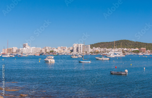 Boats, small yachts & water craft of all size in marina of Sant Antoni De Portmay. Morning of warm sunny day in the harbour. Bright town of Sant Antoni de Portmany, Balearic Islands, Spain.
