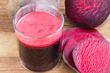 Fresh beet juice in glass and sliced beetroot on wooden table.