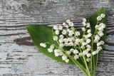 Bouquet of lilies of the valley on an old wooden background