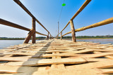 beautiful long bamboo bridge on river with blue sky at sunny day. soft focus