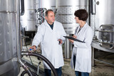 Laughing wine maker shows to expert equipment