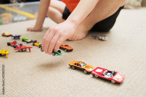 Poster boy playing with car collection on carpet