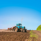 Tractor cultivating field at spring. Russian agriculture